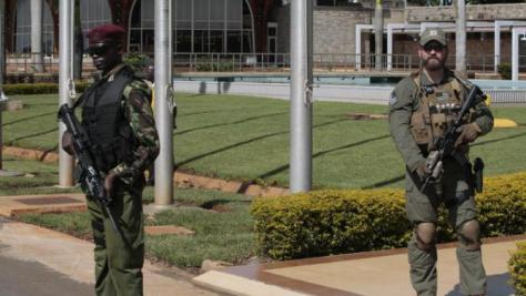 Kenyan Security Personnal , left, and U.S. security peraonnal, right secure the area at Kenytta International Airport before U.S. Secretary of State John Kerry, arrives in Nairobi, Kenya, Sunday, May 3, 2015.  Kerry is visiting Sri Lanka, Kenya, and Djibouti on his trip. (AP Photo/SAyyid Azim)